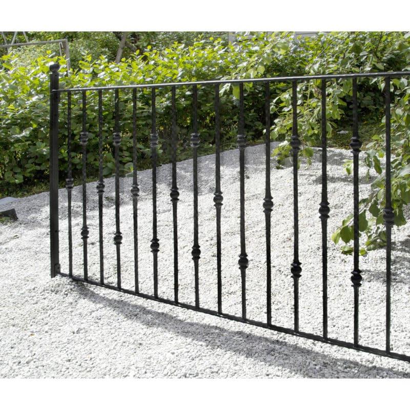 Tkorauta-aita tontin ympärille rajaamaan puutarhaa, musta metalliaita.